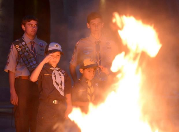Boy Scout saluting burning flags at ceremony