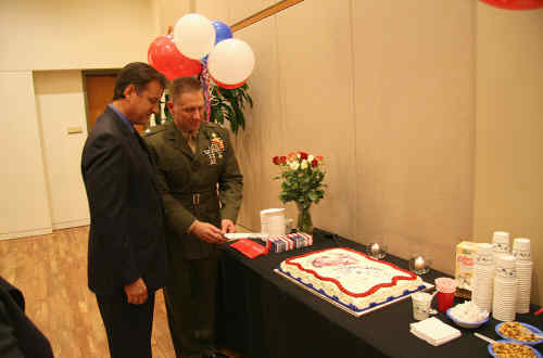 City representative and Battalion representative cutting into cake